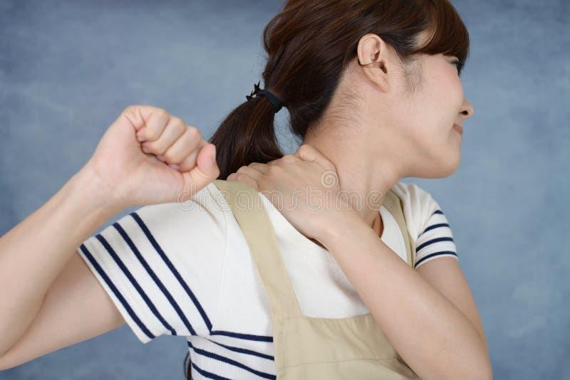 Kvinna som har en skuldra att sm?rta arkivfoto