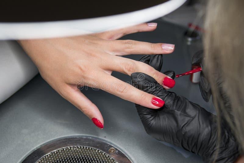 Kvinna som har en spikamanikyr i en skönhetsalong med en closeupsikt av en kosmetolog som applicerar fernissa med en applikator royaltyfri foto