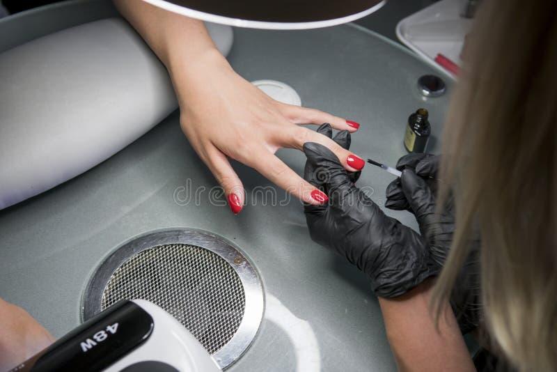 Kvinna som har en spikamanikyr i en skönhetsalong med en closeupsikt av en kosmetolog som applicerar fernissa med en applikator royaltyfri bild