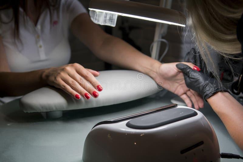 Kvinna som har en spikamanikyr i en skönhetsalong med en closeupsikt av en kosmetolog som applicerar fernissa med en applikator fotografering för bildbyråer
