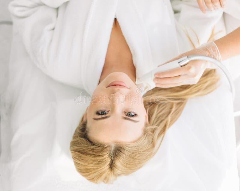 Kvinna som har en stimulerande ansikts- behandling från en terapeut royaltyfri bild