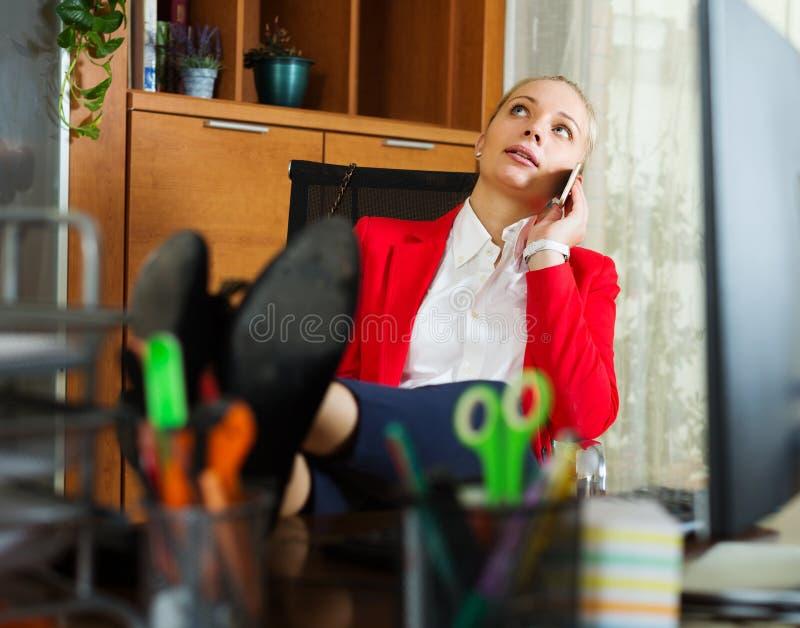 Kvinna som har en tröttande tid och talar vid mobilen royaltyfri bild