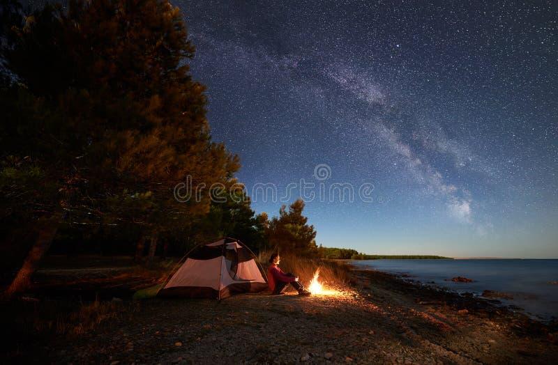 Kvinna som har en vila på natten som campar nära det turist- tältet, lägereld på havskust under stjärnklar himmel arkivbild