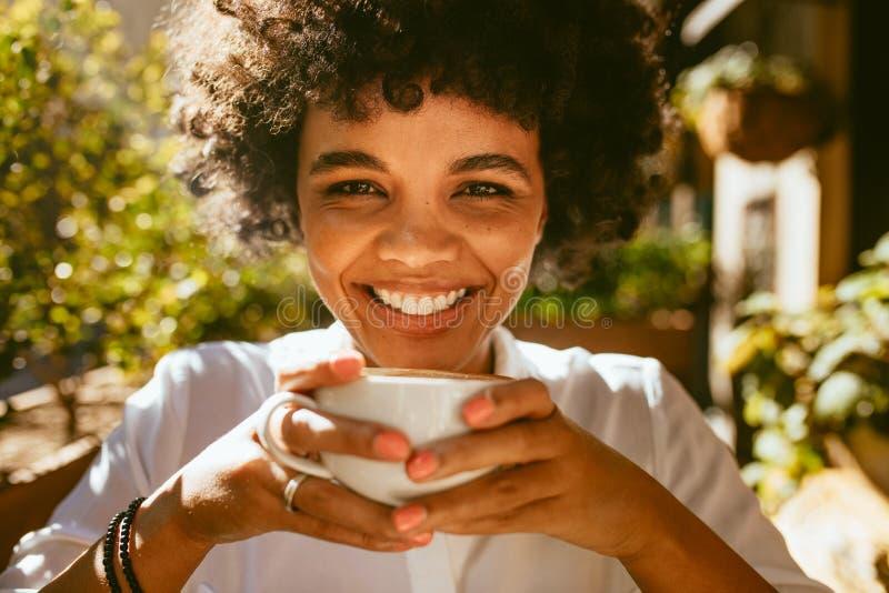 Kvinna som har ett uppfriskande kaffe arkivfoton