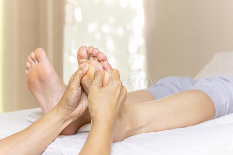 Kvinna som har fotmassage i brunnsortsalong arkivfoton