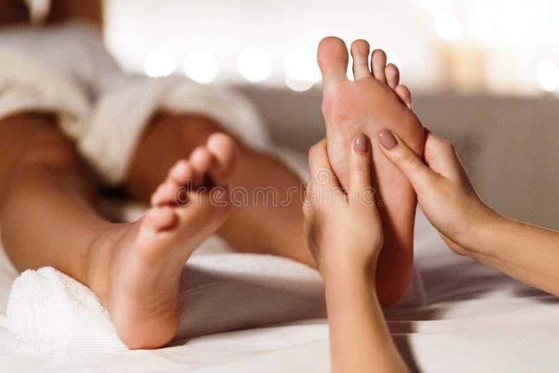 Kvinna som har fotmassagen som kopplar av i den Spa salongen royaltyfri bild