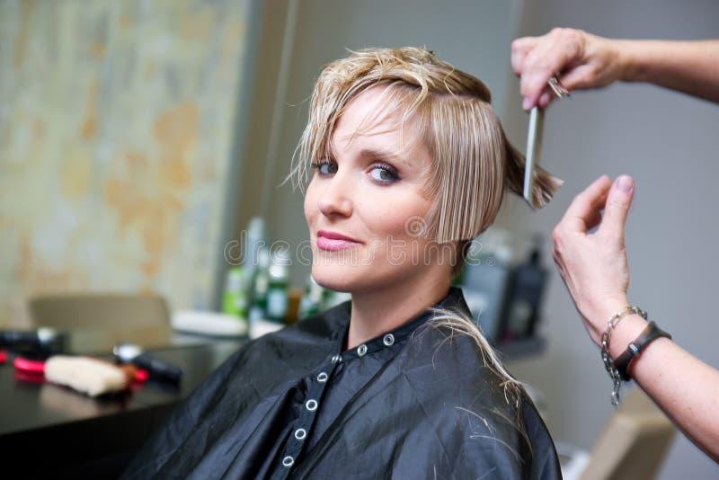 Kvinna som har frisyr royaltyfria bilder