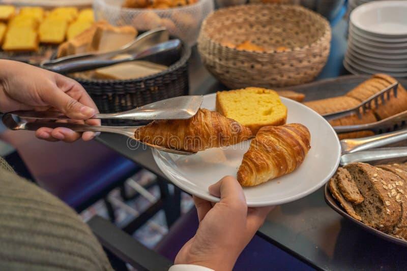Kvinna som har frukostbuffé i hotell med smörgifflet arkivfoto