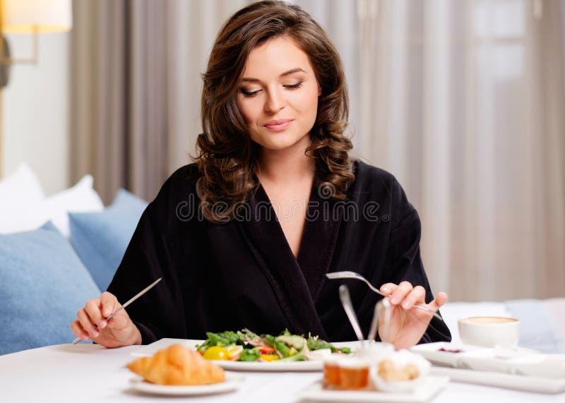 Kvinna som har frukosten i ett hotell arkivbild