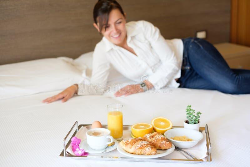 Kvinna som har frukosten i hennes hotellrum arkivbild