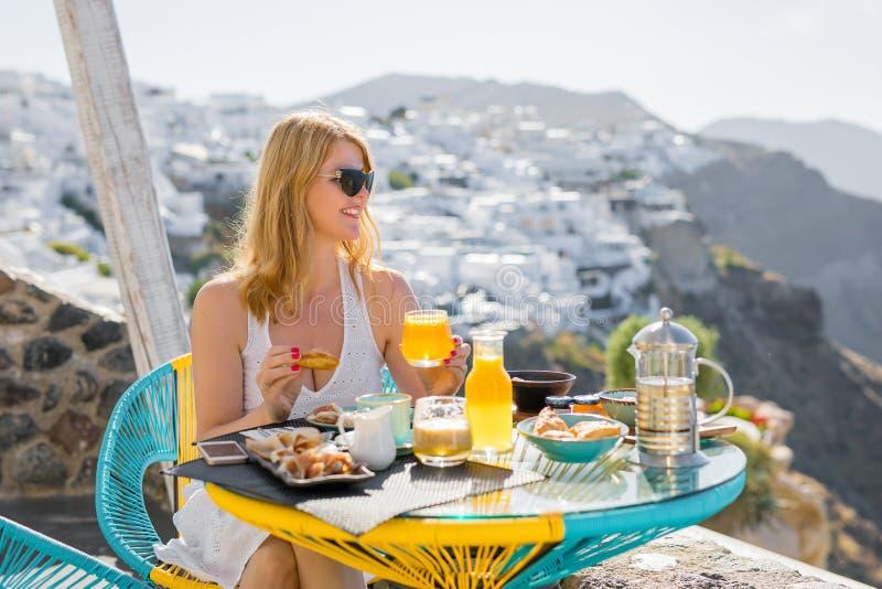 Kvinna som har frukosten i lyxigt hotell i Santorini arkivbild