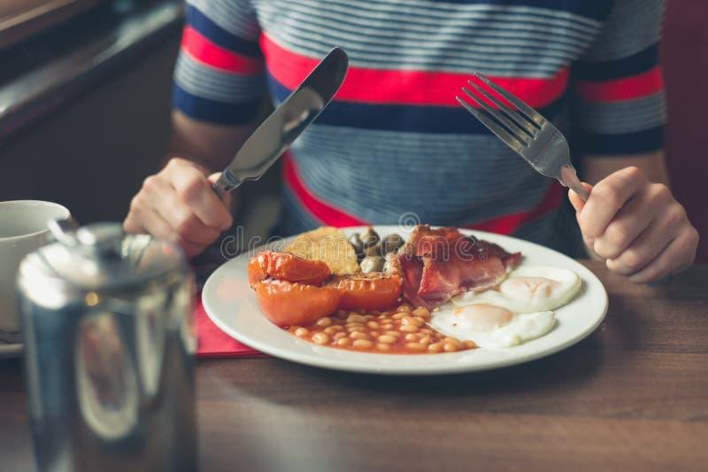 Kvinna som har frukosten i matställe arkivbilder