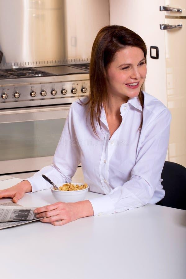 Kvinna som har frukosten och läsningtidningen arkivfoton