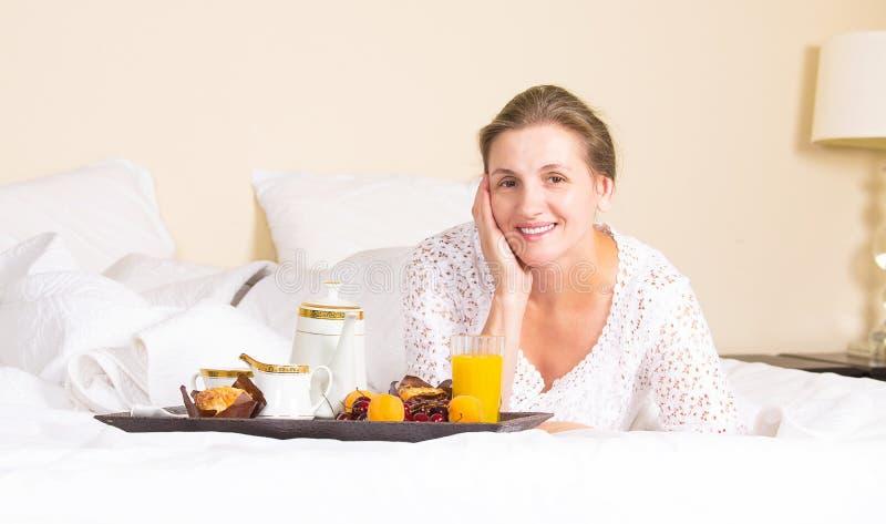 Kvinna som har frukosten som kopplar av i hotellsäng royaltyfri bild