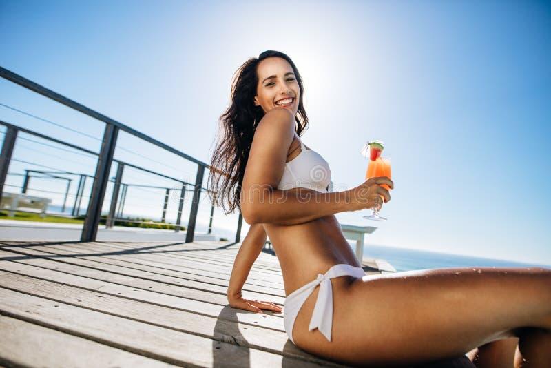 Kvinna som har gyckel p? poolsiden royaltyfri bild