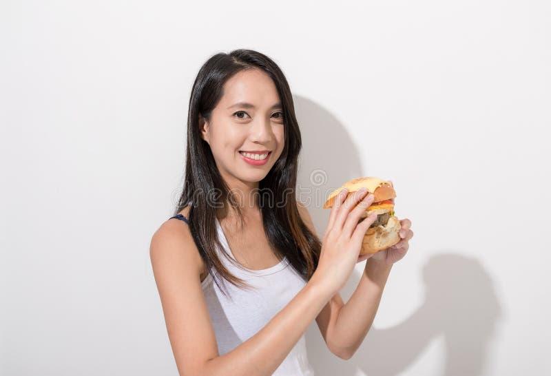 Kvinna som har hamburgaren fotografering för bildbyråer