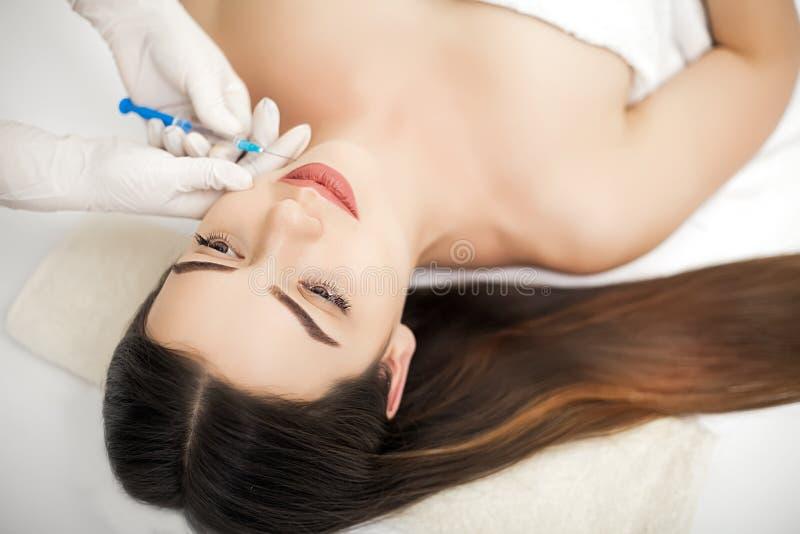 Kvinna som har injektionen i kanter som skönhetbehandling royaltyfria bilder