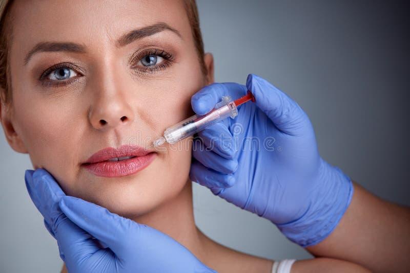 Kvinna som har injektionen i kanter, skönhetbehandling arkivfoton