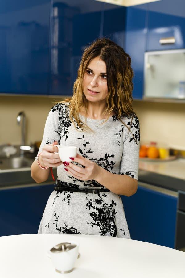 Kvinna som har kaffe hemma royaltyfria bilder