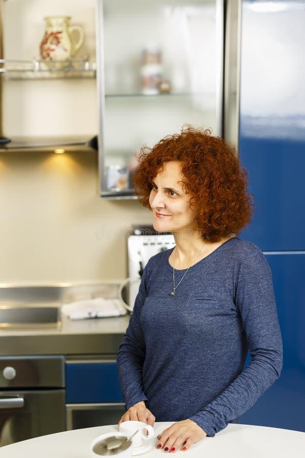 Kvinna som har kaffe hemma arkivfoto