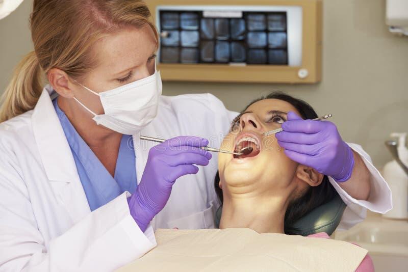 Kvinna som har kontrollen upp på tandläkarekirurgi arkivbild