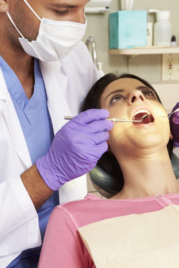 Kvinna som har kontrollen upp på tandläkarekirurgi royaltyfri bild