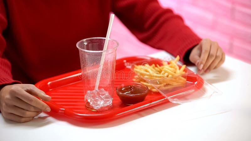 Kvinna som har lunch i snabbmatrestaurang, franska sm?fiskar och tomt exponeringsglas p? magasinet royaltyfria foton