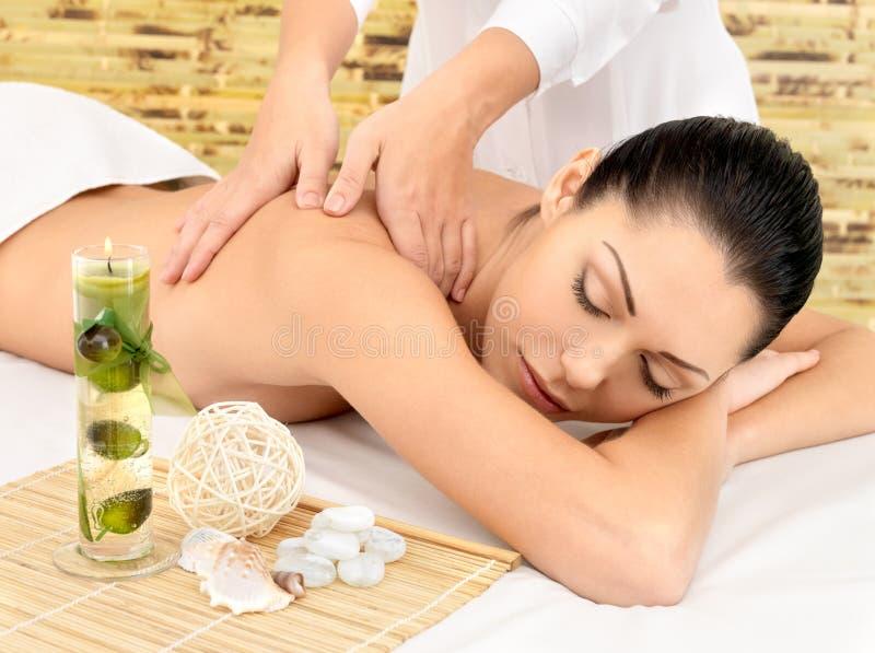 Kvinna som har massage av huvuddelen i brunnsortsalong fotografering för bildbyråer