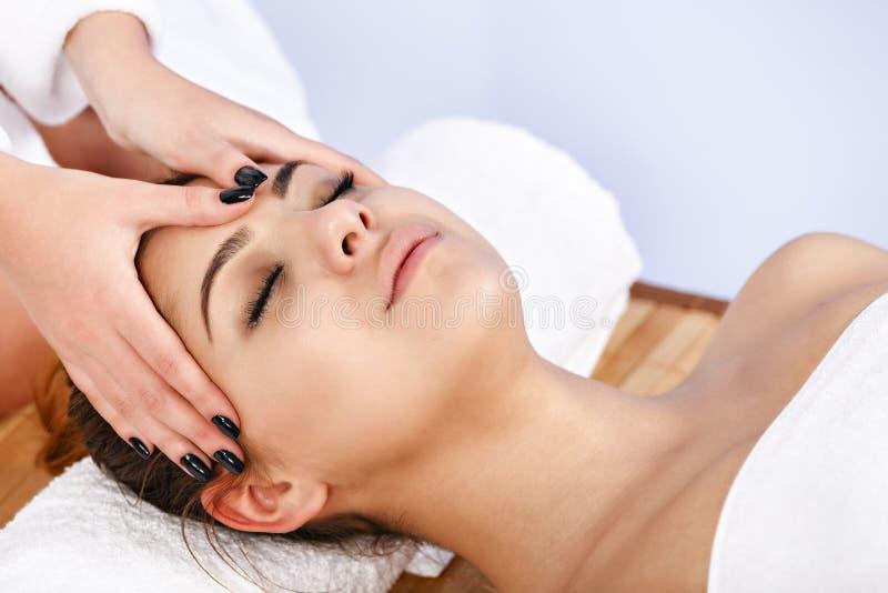Kvinna som har massage av huvuddelen i brunnsortsalongen olja för badskönhetsammansättning soaps behandling royaltyfri foto