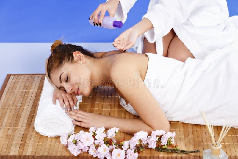 Kvinna som har massage av huvuddelen i brunnsortsalongen olja för badskönhetsammansättning soaps behandling royaltyfria foton