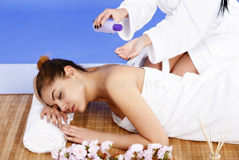 Kvinna som har massage av huvuddelen i brunnsortsalongen olja för badskönhetsammansättning soaps behandling arkivfoton