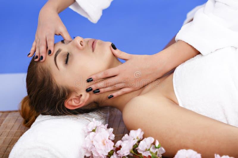 Kvinna som har massage av huvuddelen i brunnsortsalongen olja för badskönhetsammansättning soaps behandling arkivbild