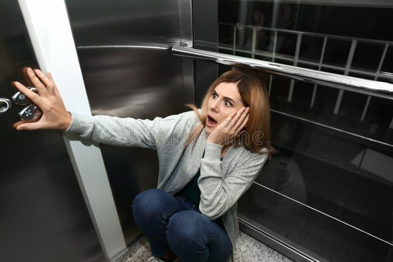 Kvinna som har nödattack i hiss arkivfoto