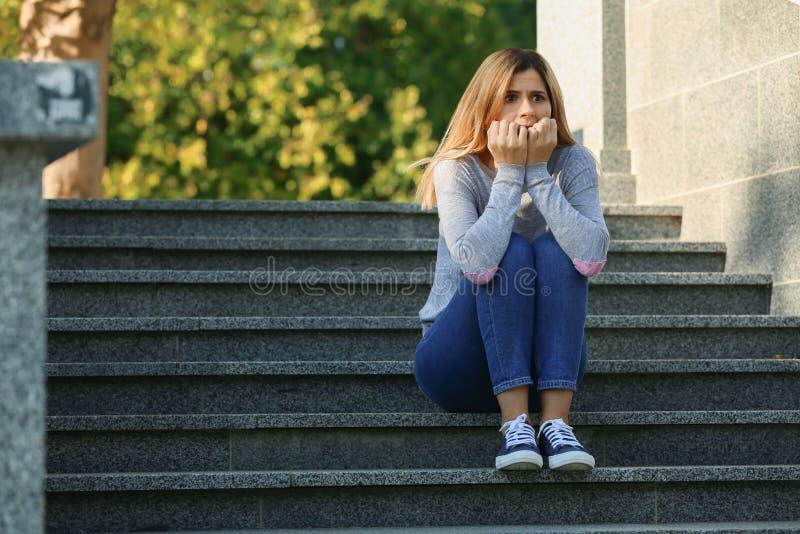 Kvinna som har nödattack, medan sitta på moment utomhus royaltyfria bilder