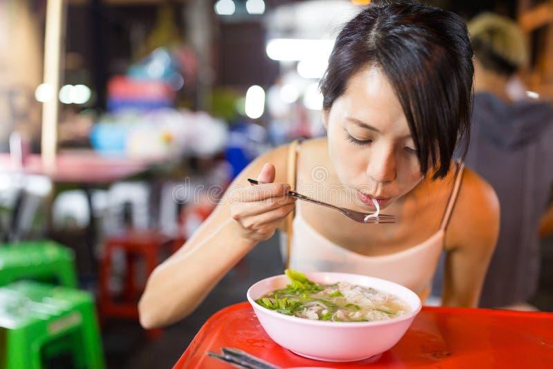 Kvinna som har nudlar i nattmarknad av den Bangkok staden royaltyfria bilder