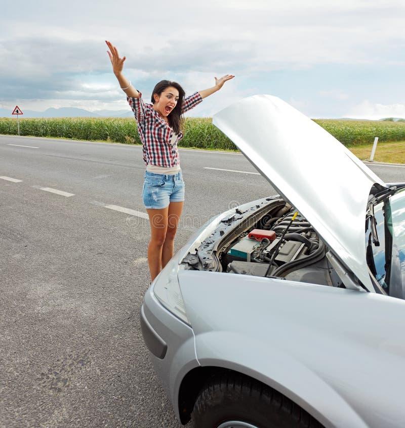 Kvinna som har problem med den brutna bilen arkivfoton
