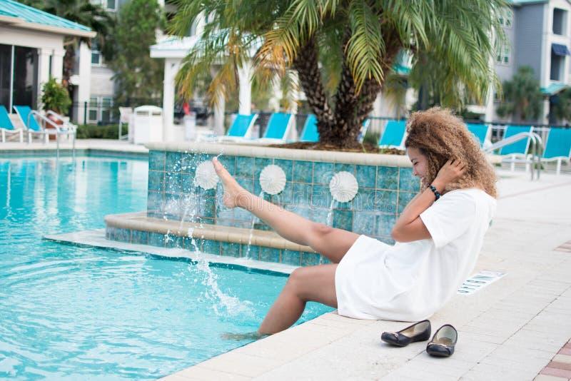 Kvinna som har roligt sammanträde vid det plaskande vattnet för pöl royaltyfri bild