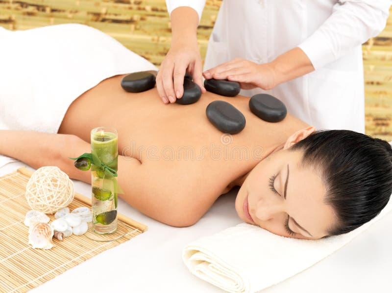 Kvinna som har stenmassage av backen i brunnsortsalong arkivbild