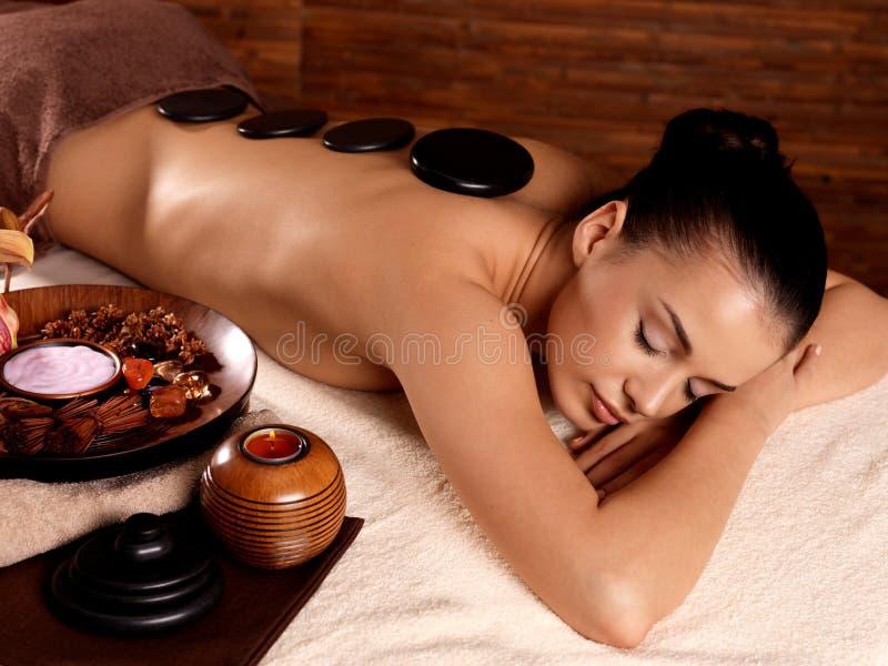 Kvinna som har stenmassage i brunnsortsalong arkivfoton
