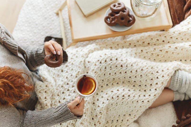 Kvinna som har te och pepparkakan arkivfoton