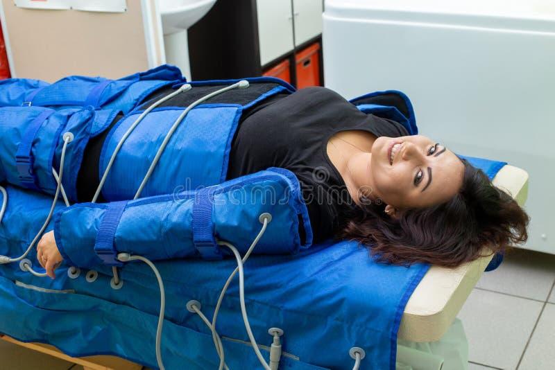 Kvinna som har tillvägagångssätt av anti-cellulitemassagen på den pressotherapy maskinen royaltyfria bilder