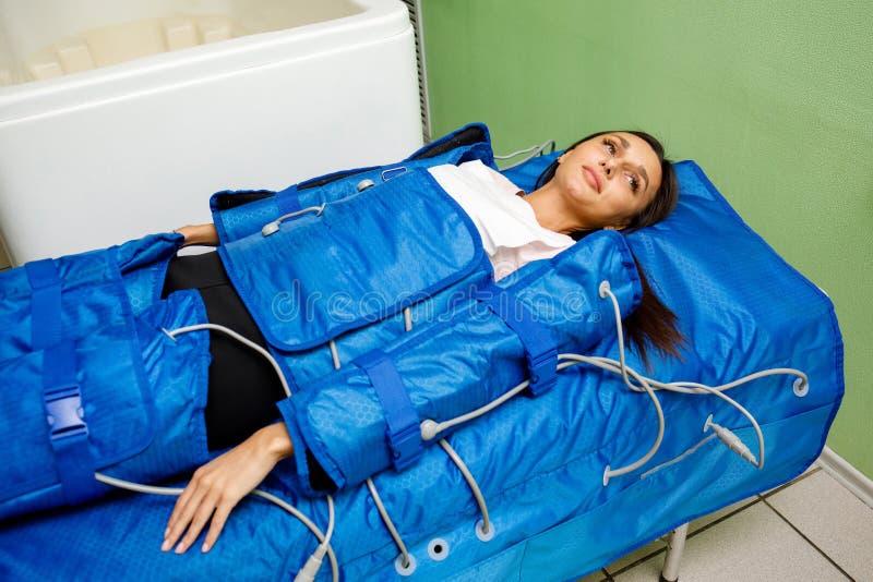 Kvinna som har tillvägagångssätt av anti-cellulitemassagen på den pressotherapy maskinen royaltyfri foto