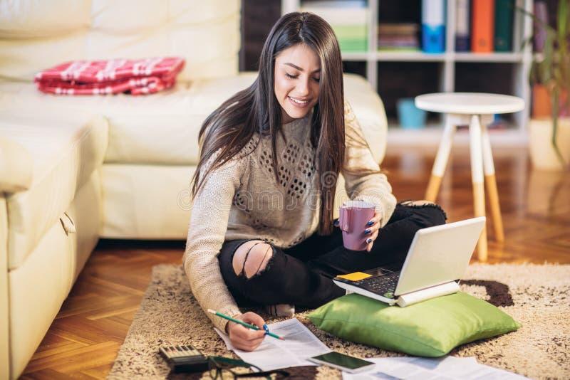 Kvinna som hemifrån arbetar och att sitta på golvet arkivfoton