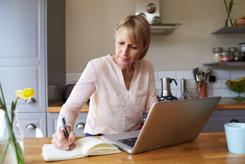 Kvinna som hemifrån arbetar på bärbara datorn i modern lägenhet arkivfoton
