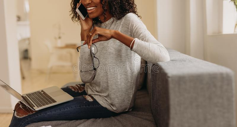 Kvinna som hemifrån klarar av affär med mobiltelefonen och bärbara datorn royaltyfri bild