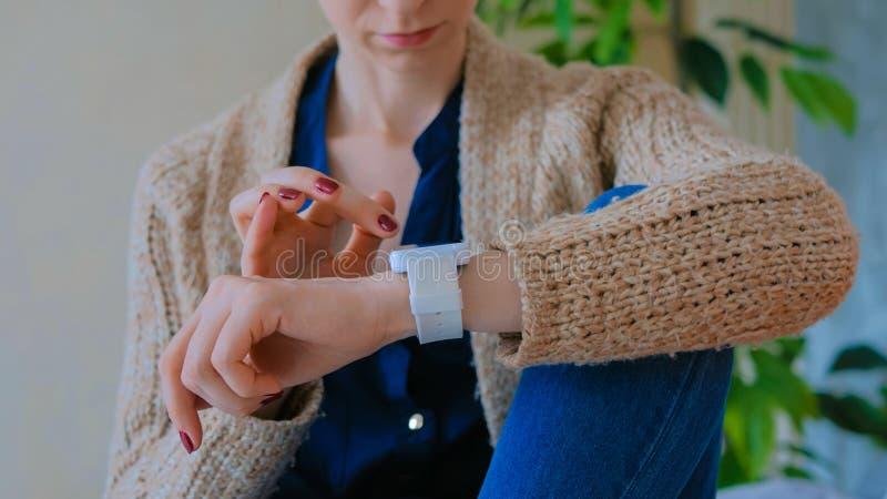 Kvinna som hemma använder den smarta klockan arkivbild