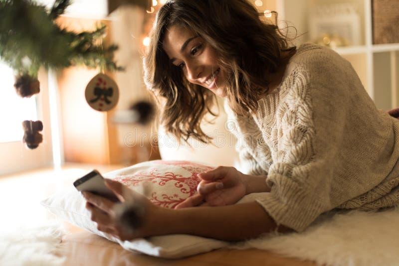 Kvinna som hemma använder en smartphone arkivbild