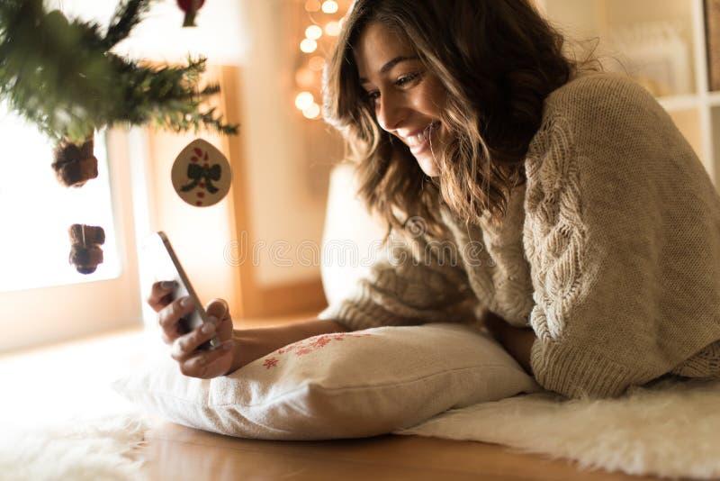 Kvinna som hemma använder en smartphone royaltyfri foto