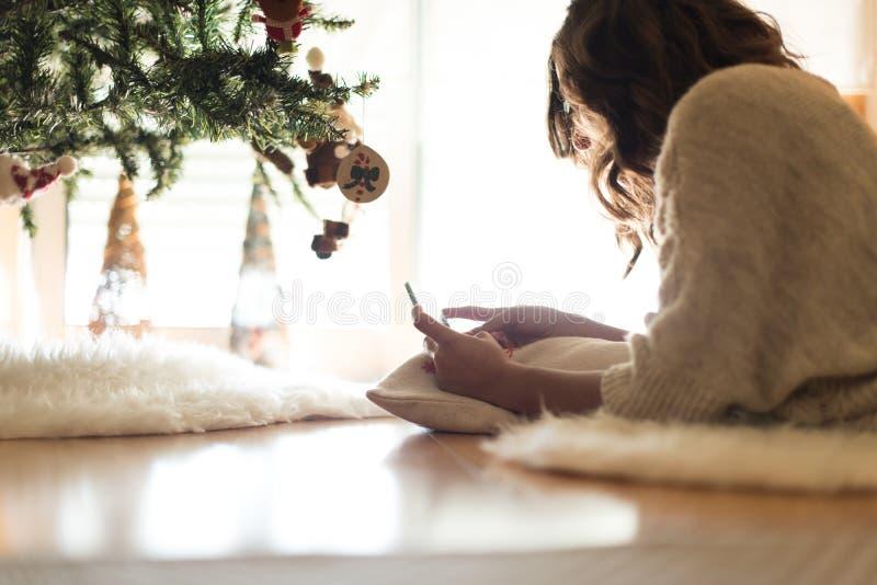 Kvinna som hemma använder en smartphone arkivfoto