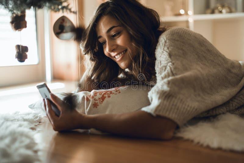 Kvinna som hemma använder en smartphone royaltyfria bilder